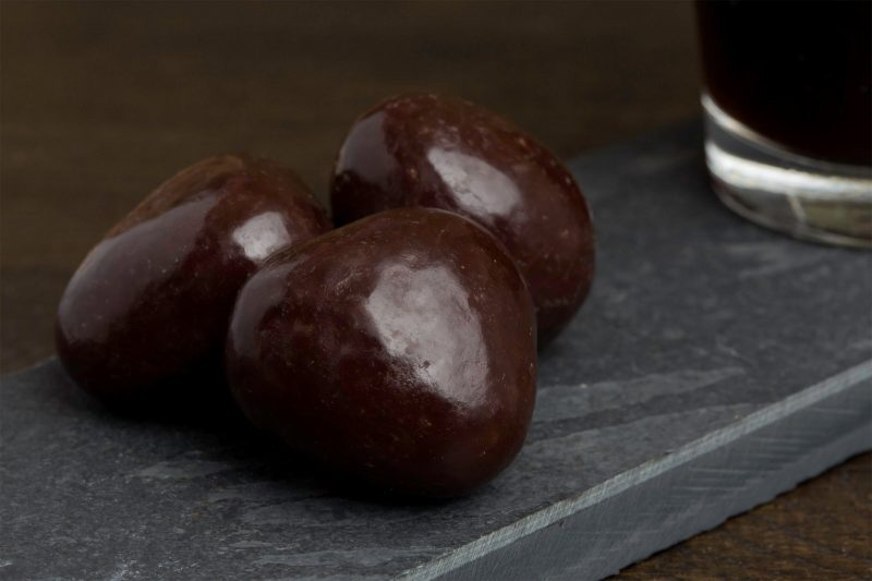 Pure chocolade en aardbei - Sfeerbeeld van de Dazzles! Fragies of Fragles neergelegd op een donkere houten tafel bij een kop koffie
