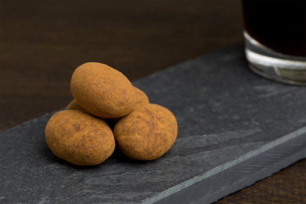 Kaneel, melkchocolade en amandel - Sfeerbeeld van de Dazzles! Arabian Nights neergelegd op een donkere houten tafel bij een kop koffie