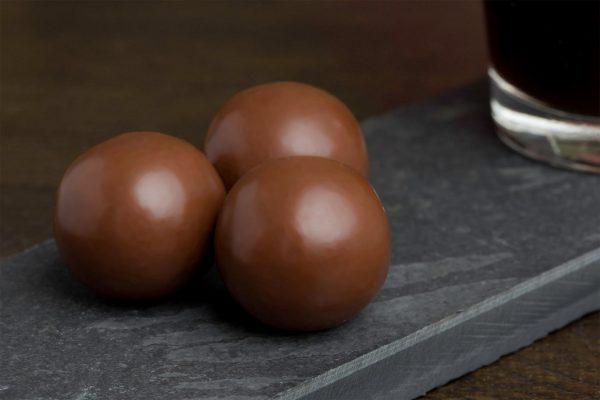 Drop fudge met melkchocolade - Sfeerbeeld van de Dazzles! Big Sweet Chocolate Salty Balls neergelegd op een donkere houten tafel bij een kop koffie