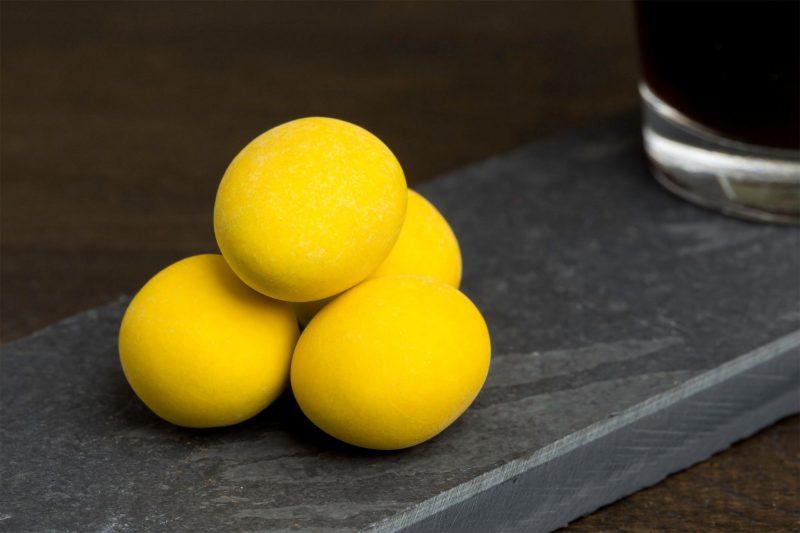 Melkchocolade, limoncello en amandel - Sfeerbeeld van de Dazzles! Tipsy Lemon Dulcis neergelegd op een donkere houten tafel bij een kop koffie