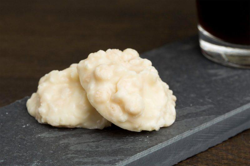 Kokos met yoghurtchocolade - Sfeerbeeld van de Dazzles! Crispy Bounty Experience neergelegd op een donkere houten tafel bij een kop koffie