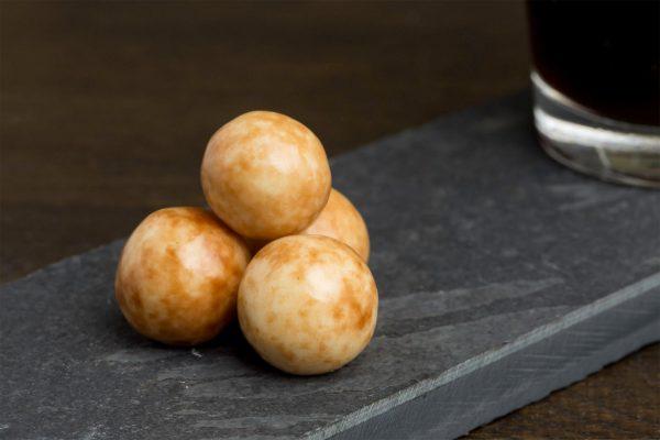 Cappuccino met witte chocolade - Sfeerbeeld van de Dazzles! Rolling Cappuccino neergelegd op een donkere houten tafel bij een kop koffie