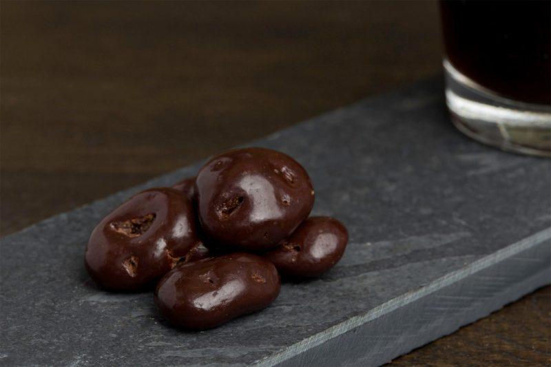 Cranberry met donkere pure chocolade - Sfeerbeeld van de Dazzles! Bitter Bite neergelegd op een donkere houten tafel bij een kop koffie