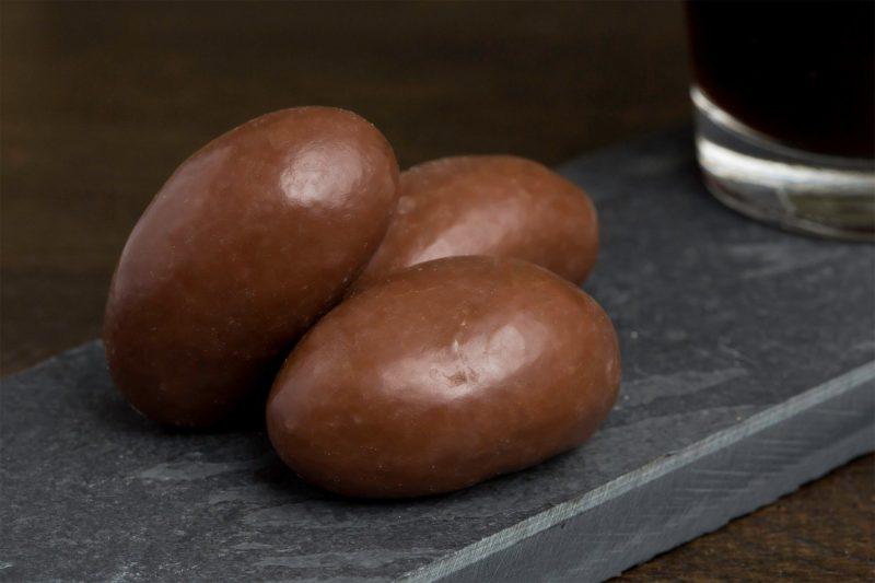 Paranoot met melkchocolade - Sfeerbeeld van de Dazzles! Brazilian Delight neergelegd op een donkere houten tafel bij een kop koffie