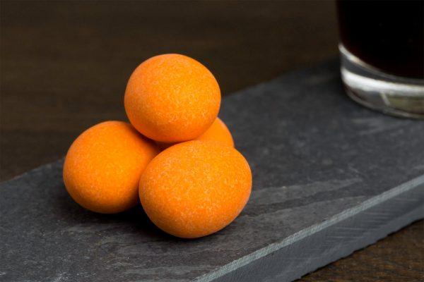 Melkchocolade, sinaasappelsmaak en amandel - Sfeerbeeld van de Dazzles! Tipsy Orange Dulcis neergelegd op een donkere houten tafel bij een kop koffie
