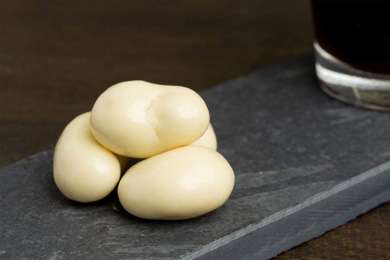 Yoghurtchocolade met cashew - Sfeerbeeld van de Dazzles! Creamy Cashew neergelegd op een donkere houten tafel bij een kop koffie