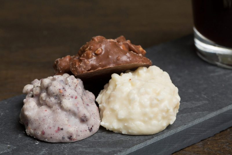 Mix van chocolade rotsjes - Sfeerbeeld van de Dazzles! Mix on the Rocks neergelegd op een donkere houten tafel bij een kop koffie