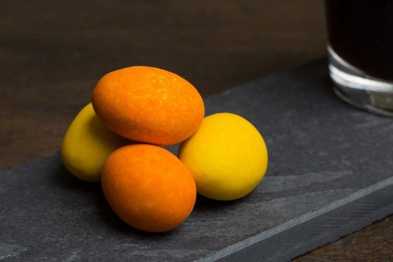 Mix met sinaasappel en limoncello in chocolade - Sfeerbeeld van de Dazzles! Tipsy Mix neergelegd op een donkere houten tafel bij een kop koffie