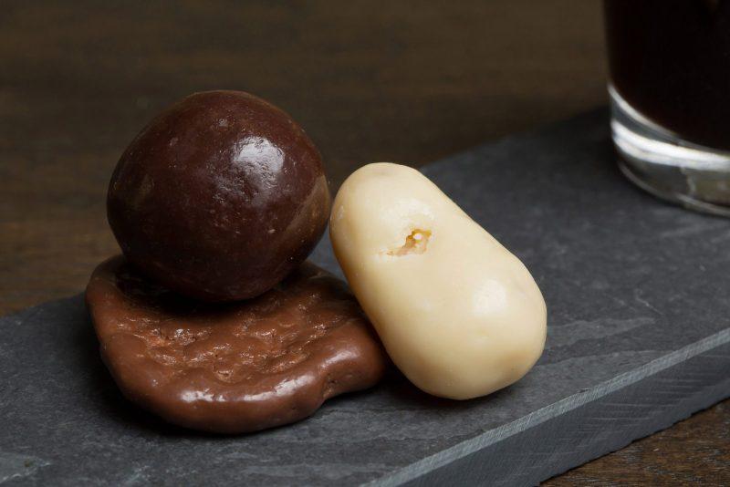 Mix van fruitige chocolade - Sfeerbeeld van de Dazzles! Fruity Mix neergelegd op een donkere houten tafel bij een kop koffie