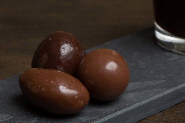 Mix van grote chocolade - Sfeerbeeld van de Dazzles! Big Mix neergelegd op een donkere houten tafel bij een kop koffie